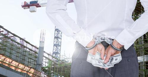 Man with handcuffs holding dollar banknotes