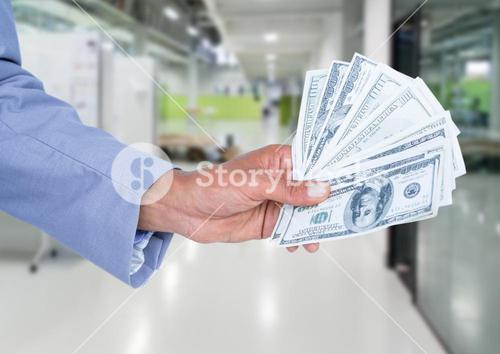 Businessman hand holding dollar banknotes