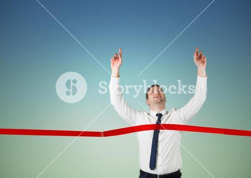 Businessman crossing finish line with arms up