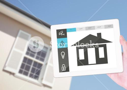 Hand holding digital tablet with home security icons