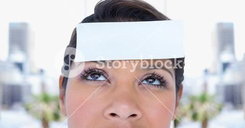 Woman with post it reminder note on forehead