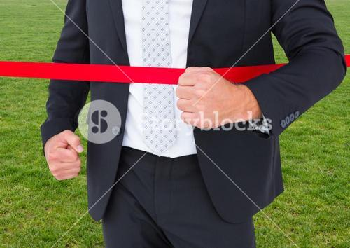 Businessman crossing finish line against green grass