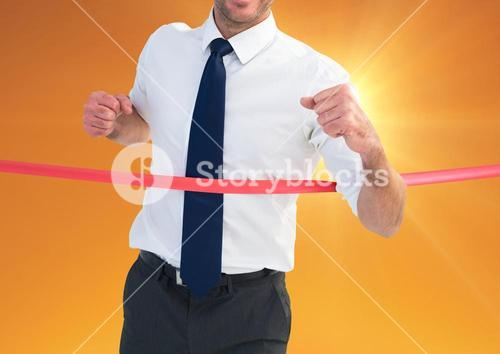 Businessman crossing finish line at dusk