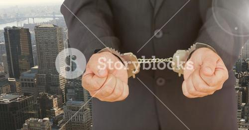 Businessman hands in handcuffs against city background