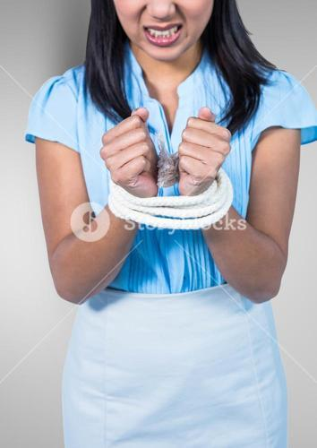 Businesswoman hands tied up with rope