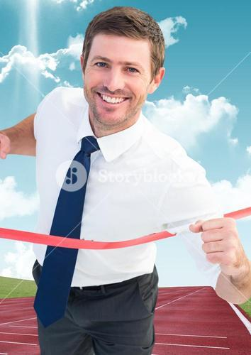 Businessman crossing finish line on a racing track