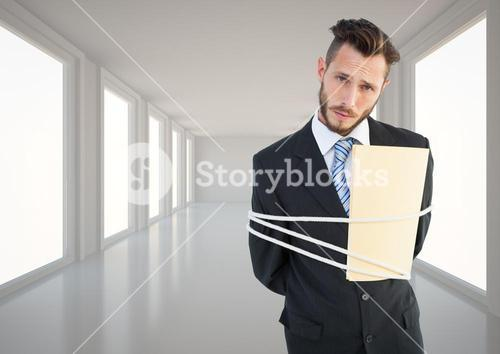 Businessman tied up in rope in corridor