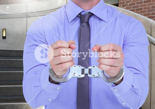 Mid section of corrupt businessman in hand cuffs
