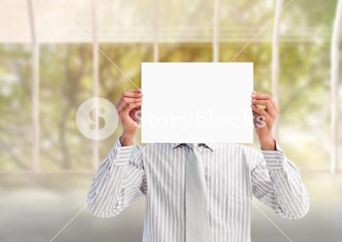Businessman holding a blank placard in front of his face