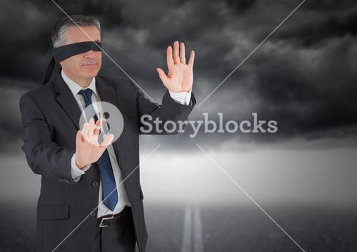 Businessman in blindfold against storm cloud