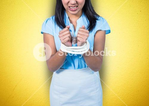 Mid section of angry businesswoman being tied up with rope