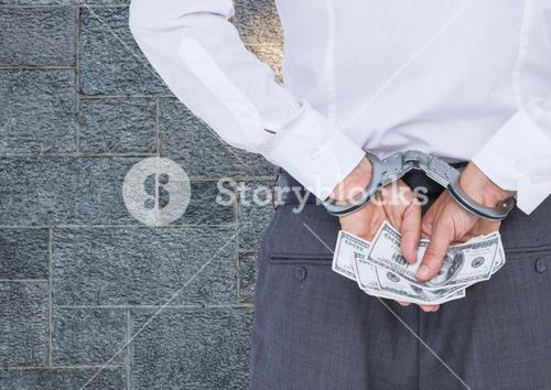 Corrupt businessman in handcuffs holding money against wall
