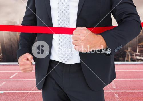 Businessman crossing the finish line in ground