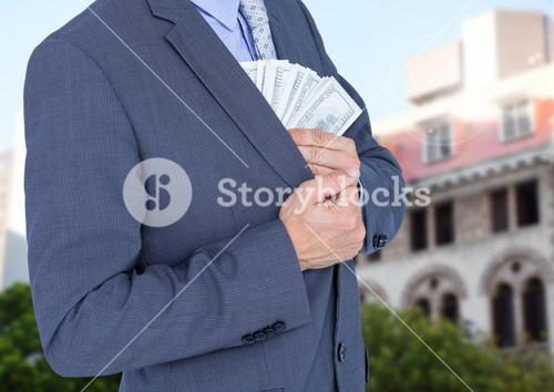 Mid section of businessman hiding money in blazer against house