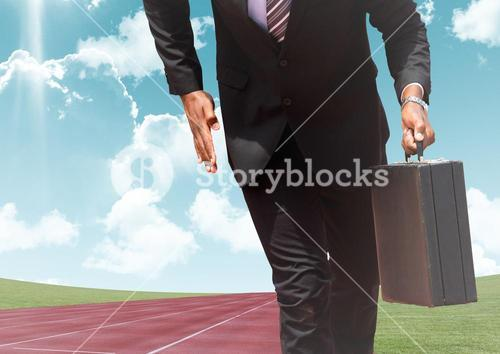 Businessman with briefcase on race track against sky in background