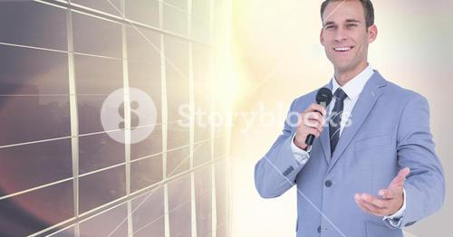 Businessman speaking with microphone against city building
