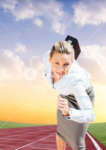 Businesswoman with briefcase running on race track
