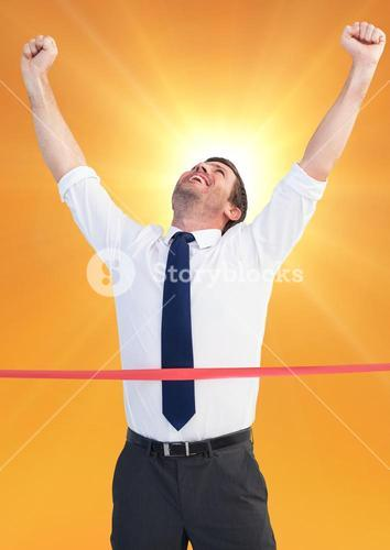 Excited businessman crossing the finish line against bright sunlight