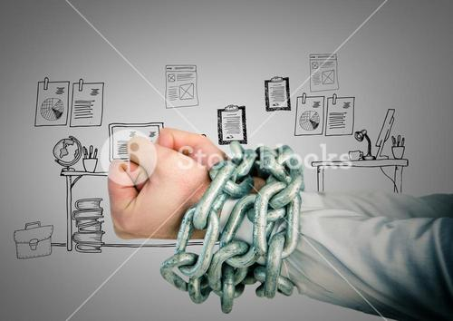 Businessman hands bound in chains against office