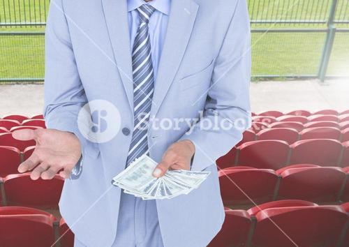 Mid section of corrupt businessman holding money in stadium
