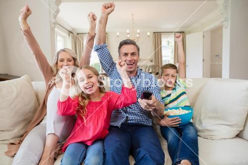 Family watching soccer match on television in living room