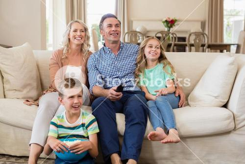 Parents and kids watching tv in living room
