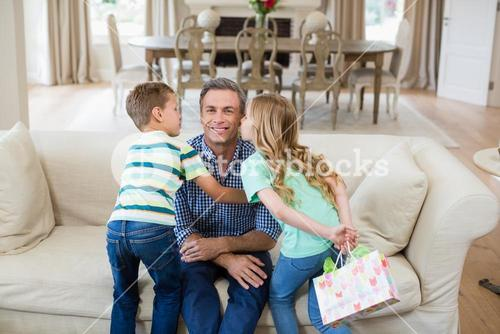 Son and daughter kissing their father on cheek in living room
