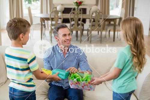 Kids giving surprised gift to their father
