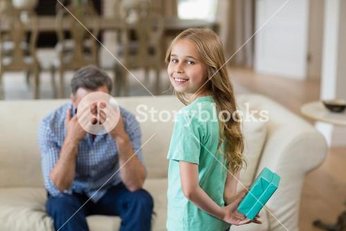 Girl holding surprised gift for her father in living room