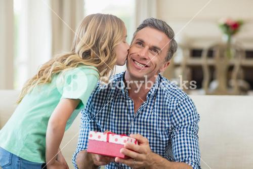 Girl kissing her father on cheek in living room