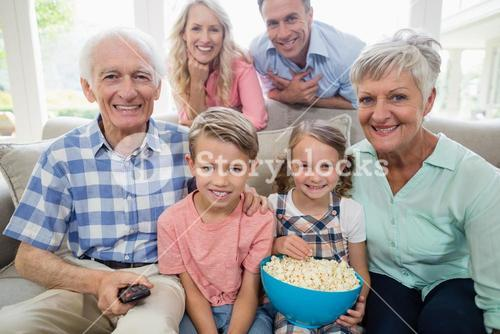 Happy multi-generation family watching television in living room