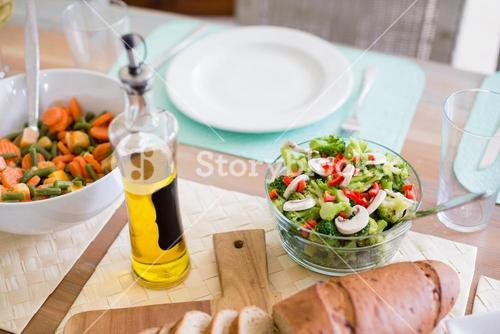 Bowl of salad and olive oil on dinning table