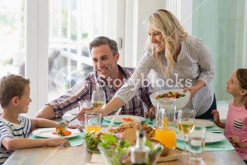 Mother serving food to family on dinning table