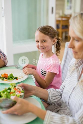 Cute girl having meal on dinning table