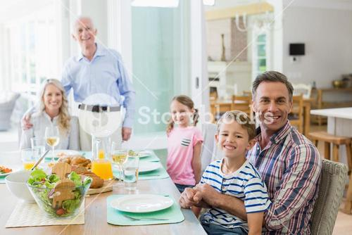 Multi- generation family having meal on dinning table at home