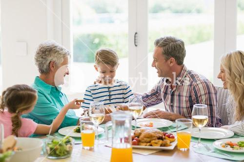Multi- generation family interacting while having meal on dinning table