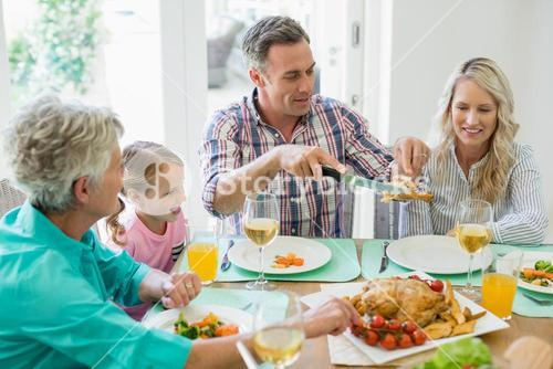 Multi- generation family having meal on dinning table
