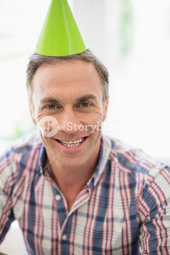 Smiling man with party hat at home
