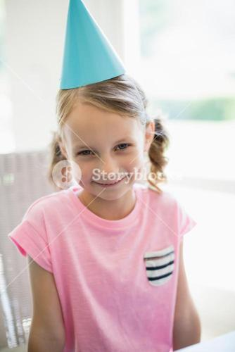 Cute girl wearing party hat at home