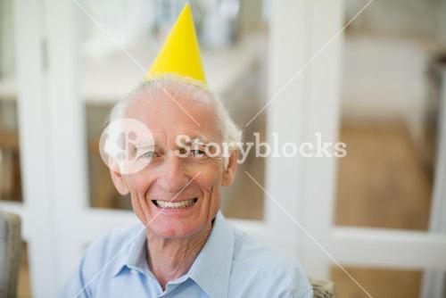Smiling senior man with party hat