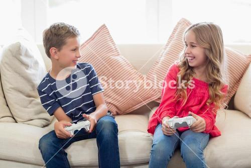 Siblings playing video games in living room