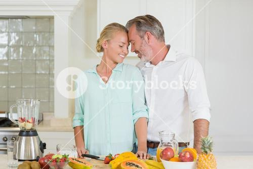 Smiling couple romancing in kitchen