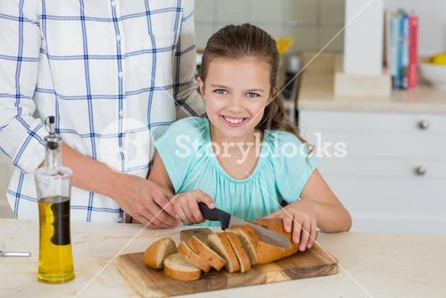Mother assisting a daughter to slice the loaf bread