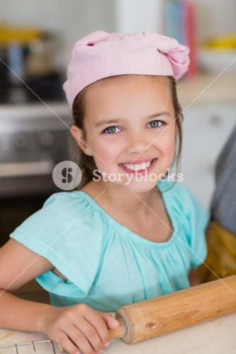 Smiling girl wearing chefs hat with rolling pin in kitchen at home