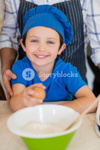 Smiling boy in chefs hat holding egg in kitchen