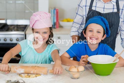 Mother and kids preparing food in kitchen