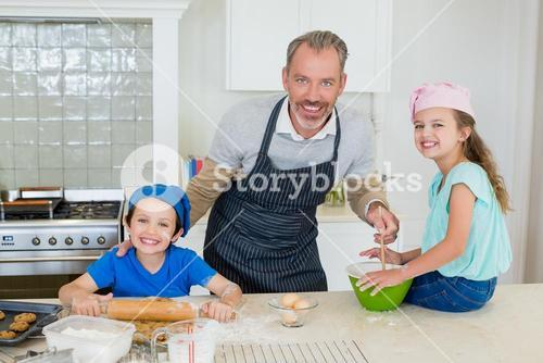Father and kids preparing food in kitchen
