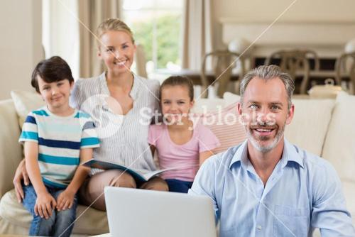 Portrait of parents and kids sitting on sofa in living room