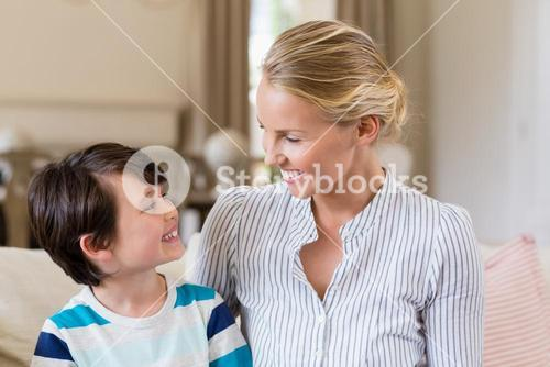 Smiling mother interacting with son in living room
