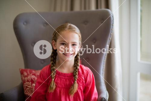 Portrait of smiling cute girl sitting on chair